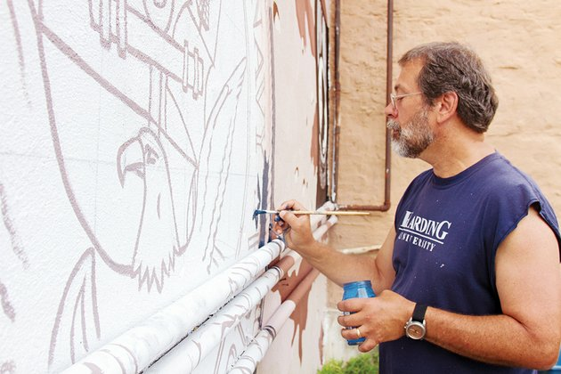 daniel-adams-professor-of-art-at-harding-university-works-on-a-mural-honoring-veterans-on-the-outside-wall-of-the-zion-climbing-center-in-downtown-searcy-the-mural-says-thank-you-to-veterans-for-their-commitment-to-the-united-states