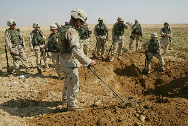 this-oct-9-2003-file-photo-shows-soldiers-from-the-us-armys-720th-military-police-battalion-watching-as-a-mine-sweeper-look-for-weapons-in-a-hole-they-dug-during-a-raid-on-a-farmland-just-outside-tikrit-iraq