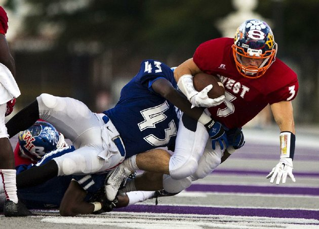 arkansas-democrat-gazettemelissa-sue-gerrits-06272014-wests-brandon-gates-is-taken-down-by-easts-demarcus-rivers-during-the-high-school-all-star-football-game-june-27-2014-at-uca-in-conway