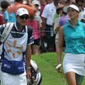 Michelle Wie talks with her caddie as they walk up the 1st fairway Friday afternoon during the first...