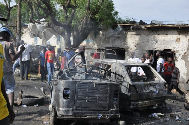 people-look-at-damaged-vehicles-at-the-scene-of-a-car-bomb-explosion-at-the-central-market-in-maiduguri-nigeria-on-tuesday-july-1-2014-a-car-bomb-exploded-in-a-market-in-nigerias-northeastern-city-of-maiduguri-on-tuesday-morning-and-dozens-of-people-are-feared-dead-witnesses-said