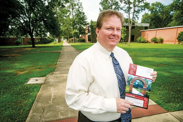 keith-pinchback-vice-chancellor-for-institutional-advancement-at-arkansas-state-university-beebe-stands-in-front-of-the-location-where-the-schools-arch-used-to-stand-he-holds-an-asu-publication-with-a-rendering-of-the-proposed-new-arch