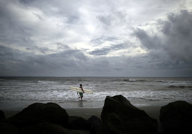 kevin-taylor-of-savannah-ga-heads-out-to-surf-the-waves-on-the-north-beach-of-tybee-island-as-hurricane-arthur-makes-its-way-up-the-east-coast-on-thursday-july-3-2014-the-storm-has-bypassed-the-georgia-coast-as-predicted-but-forecasters-are-warning-beachgoers-to-beware-of-dangerous-rip-currents-in-its-wake
