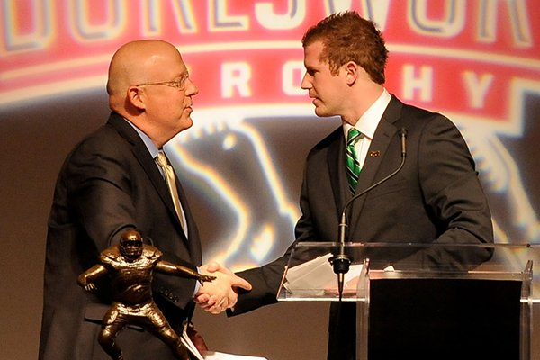 Matt McGloin, senior quarterback from Penn State, shakes hands with Chuck Barrett after accepting the Brandon Burlsworth Trophy Monday, Dec. 3, 2012 during a ceremony at the Springdale Holiday Inn Convention Center in Springdale.