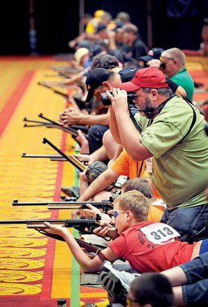 Tex Manuel II, coach of the Bull Masters from northeast Kansas, helps shooters Saturday during the 49th annual Daisy National BB Gun Championship Match held in Rogers.