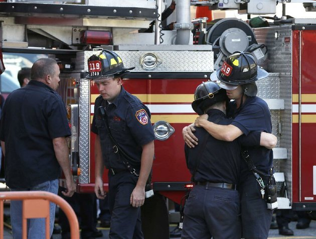firefighters-hug-one-another-after-hanging-bunting-over-the-firehouse-in-honor-of-lt-gordon-ambelas-in-new-york-sunday-july-6-2014-the-fire-department-of-new-york-is-mourning-the-death-of-ambelas-who-became-trapped-while-looking-for-victims-in-a-public-housing-high-rise-blaze-the-first-to-die-in-the-line-of-duty-in-more-than-two-years-ambelas-died-saturday-after-suffering-multiple-injuries-while-on-the-19th-floor-of-the-21-story-building-in-the-williamsburg-section-of-brooklyn-officials-said-ap-photoseth-wenig