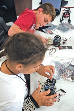 "STAFF PHOTO ANTHONY REYES Emory Brewer, 11, bottom, and Campbell Rogerson, 13, build simple robots June 27 at the Nerdies summer camp in Fayetteville. The pair were in a group building and programming robots to do simple things, in this case to act as a traffic light. The camp featured robotics, videography/creative writing and Java script with the computer game ""Minecraft."""