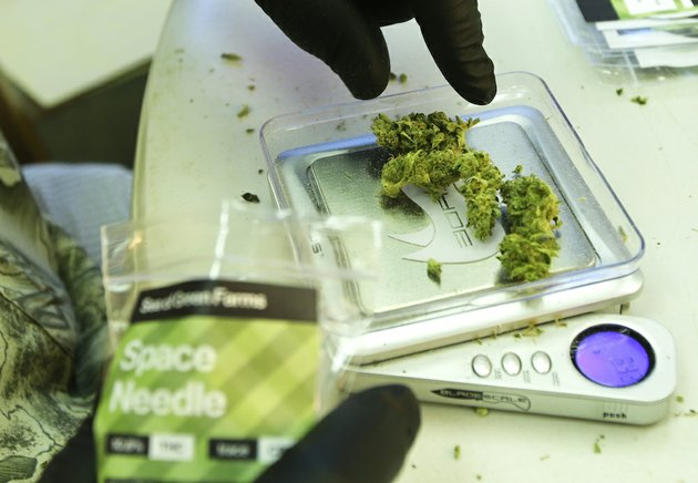 in-this-photo-taken-tuesday-july-1-2014-a-worker-weighs-out-one-gram-packets-of-a-variety-of-recreational-marijuana-named-space-needle-during-packaging-operations-at-sea-of-green-farms-in-seattle-the-grower-the-first-business-licensed-to-grow-recreational-marijuana-in-washington-state-worked-all-weekend-to-have-supplies-ready-for-stores-that-were-expected-to-be-granted-sale-licenses-on-monday-july-7-the-day-before-legal-recreational-pot-sales-begin-on-july-8