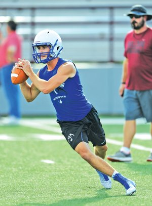 STAFF PHOTO ANDY SHUPE Cole Evans, Rogers High quarterback, rolls out to make a pass attempt while playing 7-on-7 Monday at Jarrell Williams Bulldog Stadium in Springdale.