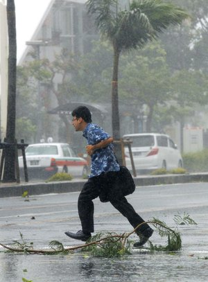 A man crosses a street amid strong winds from Typhoon Neoguri in Naha, Okinawa, southern Japan, on Tuesday.