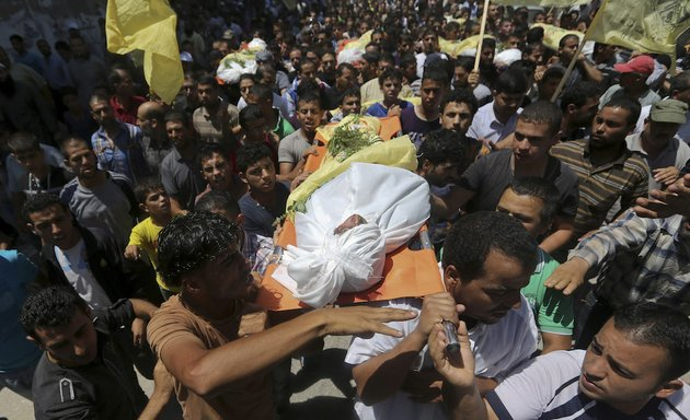 palestinians-carry-bodies-of-seven-people-killed-in-a-strike-during-their-funeral-in-khan-younis-refugee-camp-in-the-southern-gaza-strip-wednesday-july-9-2014-israel-stepped-up-its-offensive-on-the-hamas-run-gaza-strip-on-wednesday-pummeling-scores-of-targets-and-killing-over-a-dozen-of-people-as-israeli-leaders-signaled-a-weeks-long-ground-invasion-could-be-quickly-approaching-hamas-official-musheer-al-masri-said-israel-had-crossed-all-the-red-lines-and-warned-that-hamas-would-strike-back-fiercely