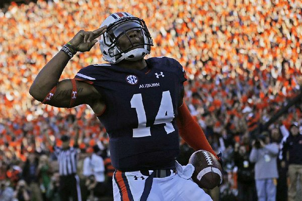 Auburn quarterback Nick Marshall (14) salutes fans after scoring against Alabama on a 45-yard touchdown run during the first half of an NCAA college football game in Auburn, Ala., Saturday, Nov. 30, 2013. (AP Photo/Dave Martin)
