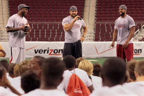Former Arkansas Razorback football players who currently play in the NFL, Darren McFadden, Peyton Hillis and DJ Williams talk to participants in the youth NFL Legends at Verizon Arena in North Little Rock on Friday.