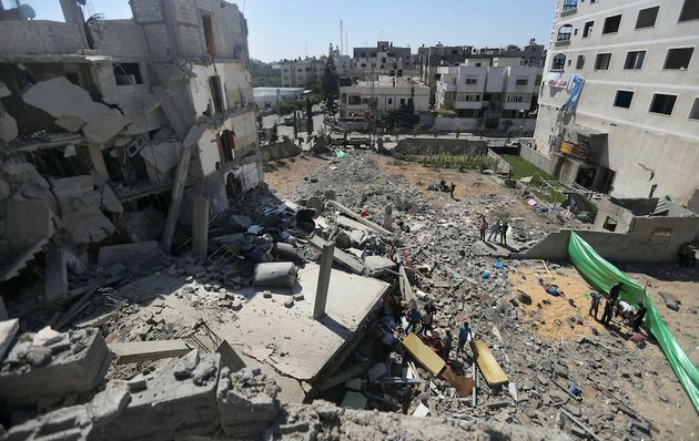 palestinians-inspect-the-rubble-of-a-building-after-it-was-hit-by-an-israeli-missile-strike-in-gaza-city-on-friday-july-11-2014-israel-launched-the-gaza-offensive-to-stop-incessant-rocket-fire-that-erupted-after-three-israeli-teenagers-were-kidnapped-and-killed-in-the-west-bank-and-a-palestinian-teenager-was-abducted-and-burned-to-death-in-an-apparent-reprisal-attack-the-military-says-it-has-hit-more-than-1100-targets-already-mostly-what-it-identified-as-rocket-launching-sites-bombarding-the-territory-on-average-every-five-minutes