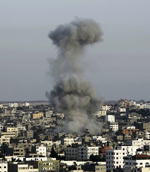 "A plume of smoke rises from an Israeli airstrike in a densely populated area of Gaza City on Saturday. Officials promised to ""raise the bar"" until Hamas is deterred from continuing its rocket attacks."