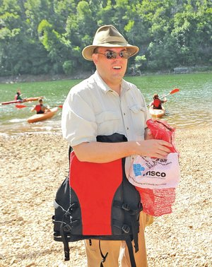 STAFF PHOTO FLIP PUTTHOFF William Armacost of Fayetteville stuffs litter in a sack before heading out with a group in kayaks Saturday.