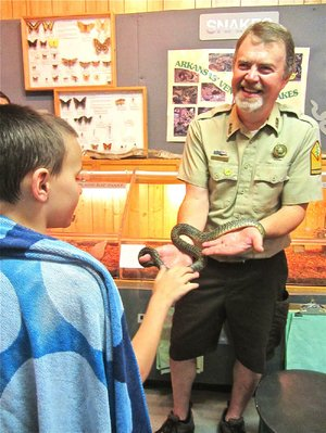 At Lake Catherine State Park, park interpreter Steve Donahou shows speckled king snake Elvis to a visitor just in from swimming and wrapped in a towel.