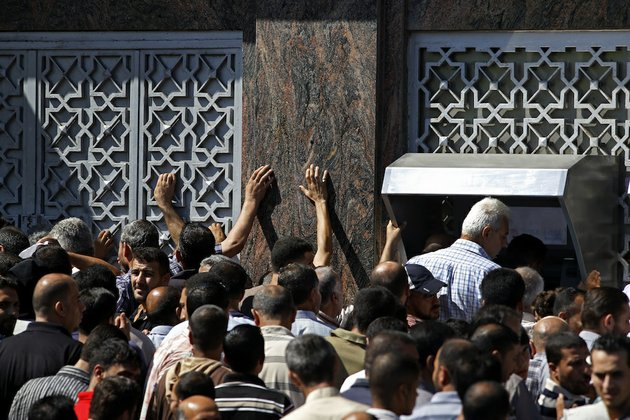 palestinians-gather-to-withdraw-money-from-atm-machines-in-gaza-city-on-thursday-july-17-2014-the-bank-of-palestine-opened-one-of-its-branches-in-gaza-citys-rimal-neighborhood-as-the-cease-fire-began-drawing-hundreds-of-people-trying-to-withdraw-money-the-israeli-military-says-it-has-struck-37-targets-in-gaza-ahead-of-a-five-hour-humanitarian-cease-fire-meant-to-allow-civilians-to-stock-up-after-10-days-of-fighting-palestinian-health-officials-say-that-in-total-at-least-225-palestinians-have-been-killed-on-the-israeli-side-one-man-was-killed-since-july-8