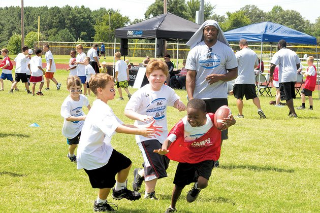 procamp-participants-run-with-the-football-after-catching-a-pass-from-carolina-panthers-running-back-jonathan-stewart