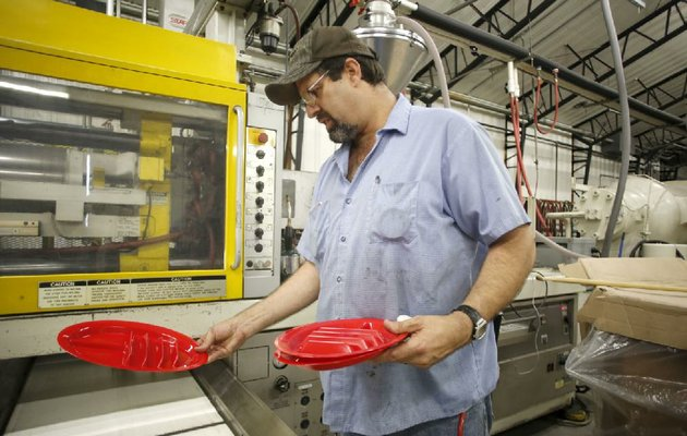 nwa-mediadavid-gottschalk-71414-steven-king-a-shift-cq-this-is-the-name-of-the-shift-supervisor-at-polytech-molding-inc-in-prairie-grove-examines-a-new-the-taco-plate-manufactured-in-a-injection-molding-machine-at-the-plant-monday-july-14-2014