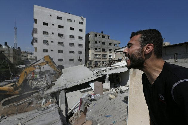 a-palestinian-gives-instructions-as-he-watches-rescuers-searching-for-bodies-and-survivors-under-the-rubble-of-an-apartment-building-destroyed-by-an-israeli-missile-strike-in-gaza-city-on-monday-july-21-2014