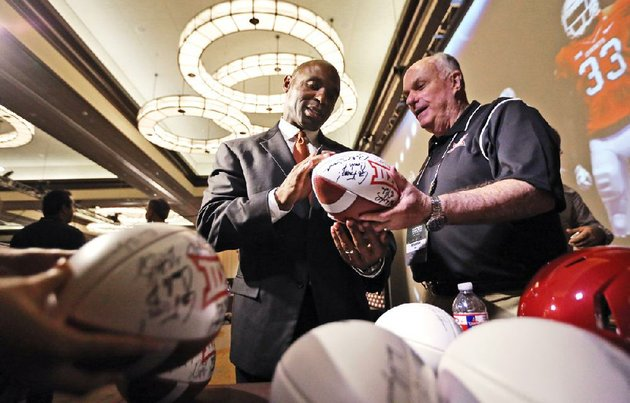 texas-head-coach-charlie-strong-left-signs-footballs-for-peter-irwin-at-the-big-12-conference-ncaa-college-football-media-days-in-dallas-tuesday-july-22-2014-ap-photo