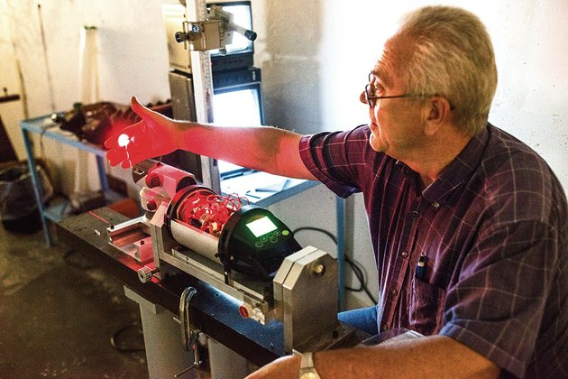 gary-young-holds-his-hand-in-the-beam-of-a-laser-he-is-calibrating-at-agl-in-jacksonville-the-company-just-celebrated-its-50th-anniversary