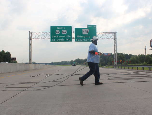 an-entergy-worker-clears-lines-that-were-knocked-down-across-us-67167-wednesday-blocking-traffic-in-both-directions
