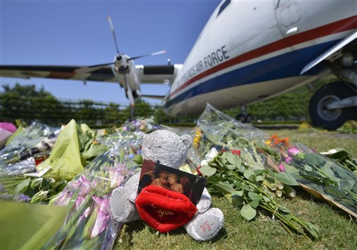 flowers-and-a-teddy-bear-are-placed-in-front-of-a-plane-prior-a-ceremony-to-mark-the-return-of-the-first-bodies-of-passengers-and-crew-killed-in-the-downing-of-malaysia-airlines-flight-17-from-ukraine-at-eindhoven-military-air-base-on-wednesday-july-23-2014-after-being-removed-from-the-planes-the-bodies-are-to-be-taken-in-a-convoy-of-hearses-to-a-military-barracks-in-the-central-city-of-hilversum-where-forensic-experts-will-begin-the-painstaking-task-of-identifying-the-bodies-and-returning-them-to-their-loved-ones