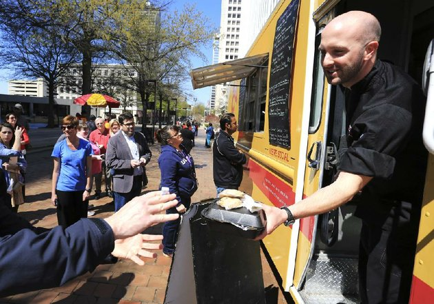 arkansas-democrat-gazetterick-mcfarland-040513-justin-patterson-hands-out-finished-orders-from-the-southern-gourmasian-truck-to-patrons-visiting-the-main-street-food-truck-fridays-in-little-rock-friday-the-first-day-of-the-event-which-runs-through-june-14