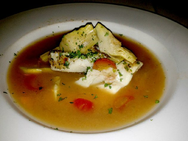 tuscan-style-cod-fillets-with-tomatoes-olives-and-artichoke-hearts-in-a-seafood-broth-at-ristorante-capeo