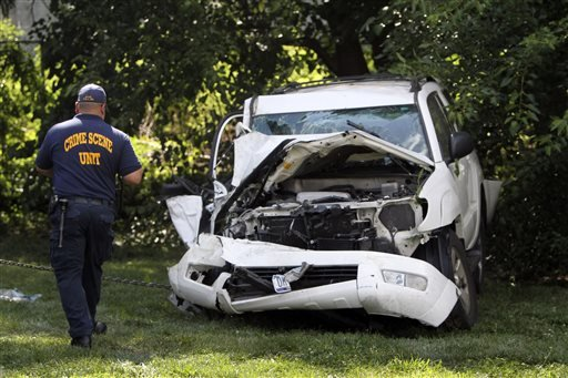 an-investigator-examines-a-heavily-damaged-suv-before-it-is-towed-from-the-scene-of-a-fatal-accident-in-north-philadelphia-friday-july-25-2014-two-children-were-killed-and-three-people-critically-injured-when-a-hijacked-car-lost-control-and-hit-a-group-of-people-near-a-fruit-stand-according-to-police