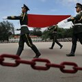 In this June 29, 2014 photo, soldiers carry a Chinese national flag at a military base during an ope...