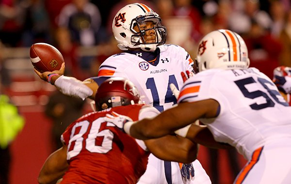 Auburn quarterback Nick Marshall is pressured by Arkansas defensive end Trey Flowers during the third quarter of their game Saturday, Nov. 2, 2013 at Razorback Stadium in Fayetteville.