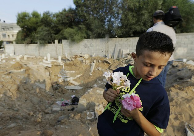 palestinian-saeb-afana-12-stands-on-the-edge-of-a-large-crater-from-an-israeli-missile-strike-that-destroyed-several-graves-as-he-carries-flowers-at-a-cemetery-in-gaza-city-in-the-northern-gaza-strip-on-monday-july-28-2014-to-visit-the-grave-of-a-relative-ayman-afana-24-who-had-been-killed-in-an-airstrike-in-the-sheik-radwan-neighborhood-some-10-days-ago