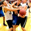 Photo by Mike Eckels A Rogers Mountie player gets caught in a Bulldog sandwich as Victor Urquidi (left) and Jay Porter (right) fight to gain possession of the basketball during the Rogers/Decatur game July 24 at the Gentry High School gym.