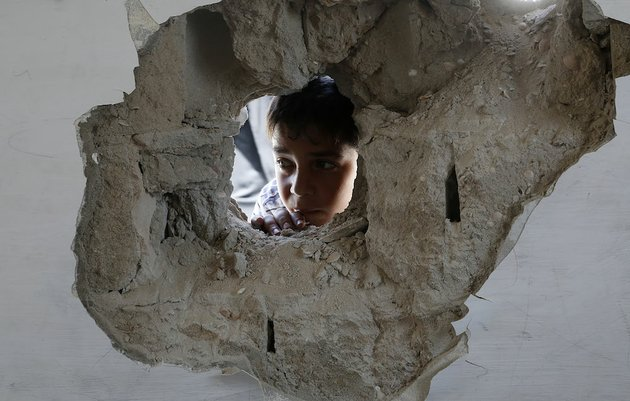 a-boy-looks-through-a-hole-on-the-wall-made-after-an-israel-strike-at-the-abu-hussein-un-school-in-the-jebaliya-refugee-camp-in-the-northern-gaza-strip-on-wednesday-july-30-2014