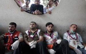 Palestinian medical workers take a break Wednesday at Shifa Hospital in Gaza City after carrying those wounded in an Israeli airstrike on a market in the Shijaiyah neighborhood.