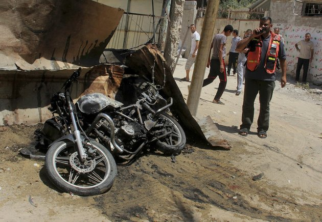 a-palestinian-medic-inspects-the-wreckage-of-a-motorcycle-caused-by-an-israeli-airstrike-in-rafah-on-thursday-july-31-2014-fadel-elmeghary-an-islamic-jihad-member-was-killed-in-the-airstrike-while-on-his-motorcycle-in-rafah-according-to-gaza-health-official-ashraf-al-kidra