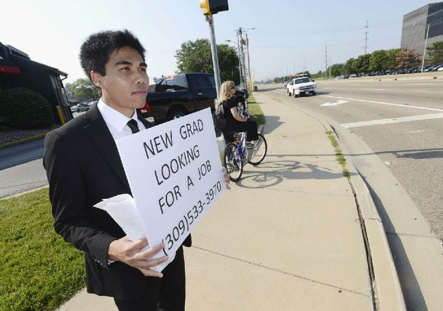 in-this-july-22-2014-photo-danu-phromrat-a-recent-illinois-state-university-economics-graduate-stands-on-a-busy-intersection-holding-a-sign-looking-for-a-job-in-bloomington-ill-phromrat-27-of-thailand-was-also-handing-out-resumes-to-motorists-who-showed-interest-phromrat-spent-four-days-trying-and-was-hired-tuesday-july-29-by-a-commercial-and-residential-construction-company-in-bloomington-as-a-full-time-accounting-assistant-ap-photothe-pantagraph-steve-smedley
