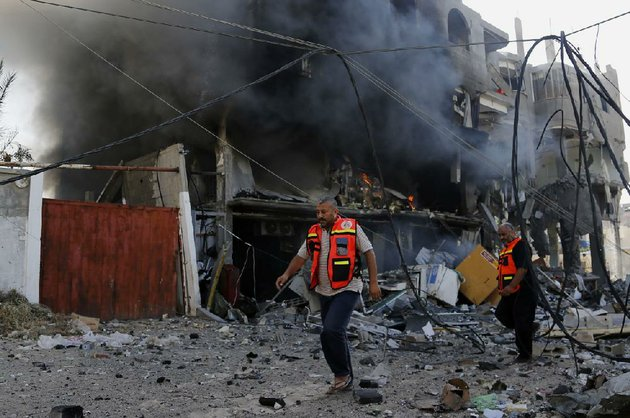 palestinian-firefighters-work-around-the-burning-rubble-of-a-milk-factory-in-gaza-city-that-was-hit-thursday-by-an-israeli-airstrike