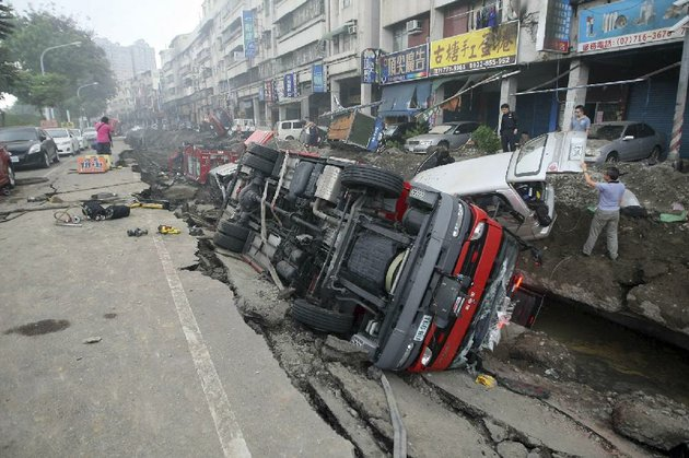 people-inspect-vehicles-tipped-over-following-multiple-explosions-from-an-underground-gas-leak-in-kaohsiung-taiwan-early-friday-aug-1-2014-a-massive-gas-leakage-early-friday-caused-five-explosions-that-killed-scores-of-people-and-injured-over-200-in-the-southern-taiwan-port-city-of-kaohsiung-ap-photo-taiwan-out