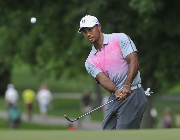 tiger-woods-watches-his-chip-to-the-fourth-hole-during-the-first-round-of-the-bridgestone-invitational-golf-tournament-thursday-july-31-2014-in-akron-ohio