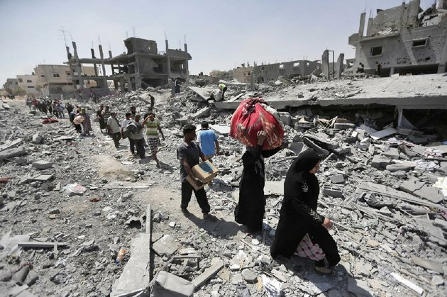 palestinians-carry-their-belongings-after-salvaging-them-from-their-destroyed-houses-in-the-heavily-bombed-town-of-beit-hanoun-gaza-strip-close-to-the-israeli-border-friday-aug-1-2014-a-three-day-gaza-cease-fire-that-began-friday-quickly-unraveled-with-israel-and-hamas-accusing-each-other-of-violating-the-truce-ap-photolefteris-pitarakis