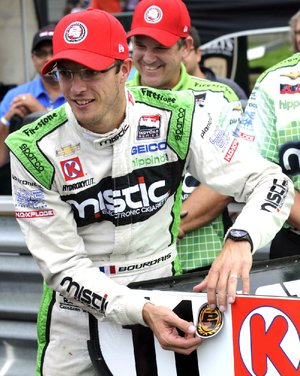 Sebastien Bourdais, of France, places the pole position sticker on the wing of his car after winning the pole for Sunday's IndyCar Honda Indy 200 auto race at Mid-Ohio Sports Car Course in Lexington, Ohio, Saturday, Aug. 2, 2014. (AP Photo/Tom E. Puskar)