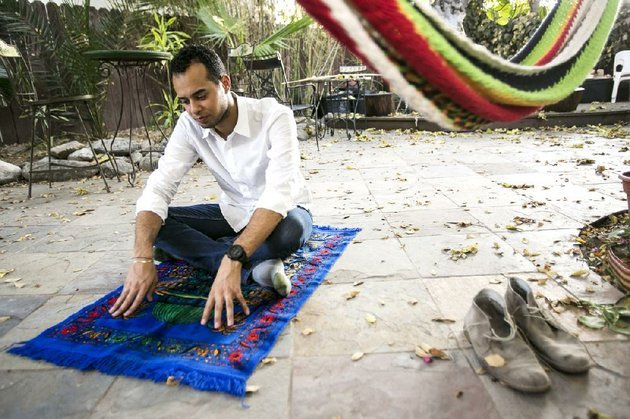 american-muslim-omar-akersim-26-poses-for-a-photo-on-his-prayer-rug-at-his-home-in-los-angeles-friday-aug-1-2014-nearly-40-percent-of-the-estimated-275-million-muslims-in-the-us-are-american-born-and-the-number-is-growing-with-the-muslim-population-skewing-younger-than-the-us-population-at-large-according-to-a-2011-survey-by-the-pew-research-center-ap-photodamian-dovarganes