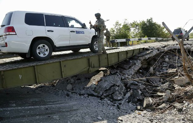 a-convoy-of-international-forensic-experts-and-members-of-the-osce-mission-in-ukraine-travel-across-a-damaged-bridge-near-debaltsevo-village-eastern-ukraine-sunday-aug-3-2014-as-they-travel-to-of-the-malaysia-airlines-flight-17-plane-crash-site-ap-photodmitry-lovetsky