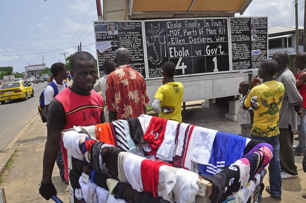 a-man-selling-clothes-walks-past-people-reading-the-comments-on-current-events-in-liberia-including-the-deadly-ebola-virus-written-by-social-commentator-alfred-sirleaf-on-a-blackboard-in-monrovia-liberia-on-saturday-aug-2-2014