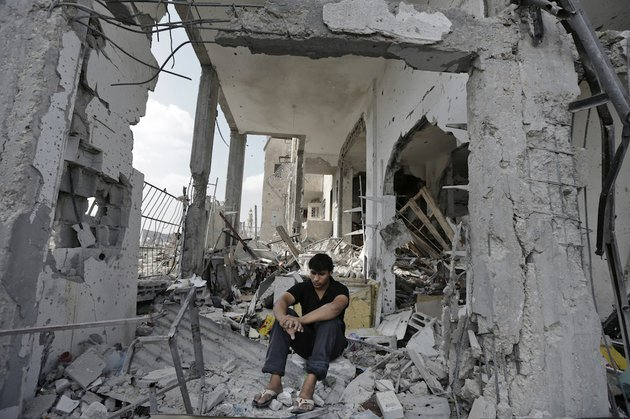 palestinian-fadi-ehajela-20-sits-on-the-rubble-of-what-used-to-be-his-familys-supermarket-on-the-ground-floor-of-the-nada-towers-at-a-residential-neighborhood-in-the-town-of-beit-lahiya-northern-gaza-strip-on-tuesday-aug-5-2014-the-supermarket-which-staffed-ten-people-and-his-nearby-family-home-were-destroyed-in-an-israeli-strike-according-to-ehajela-the-family-have-now-found-refuge-in-a-un-school-as-thousands-of-other-palestinians