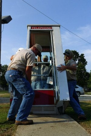Workers for the Prairie Grove Telephone Co. put the phone booth back in place Tuesday in front of the Colonial Motel, where it had sat since 1959 until it was knocked down by an SUV on June 7.